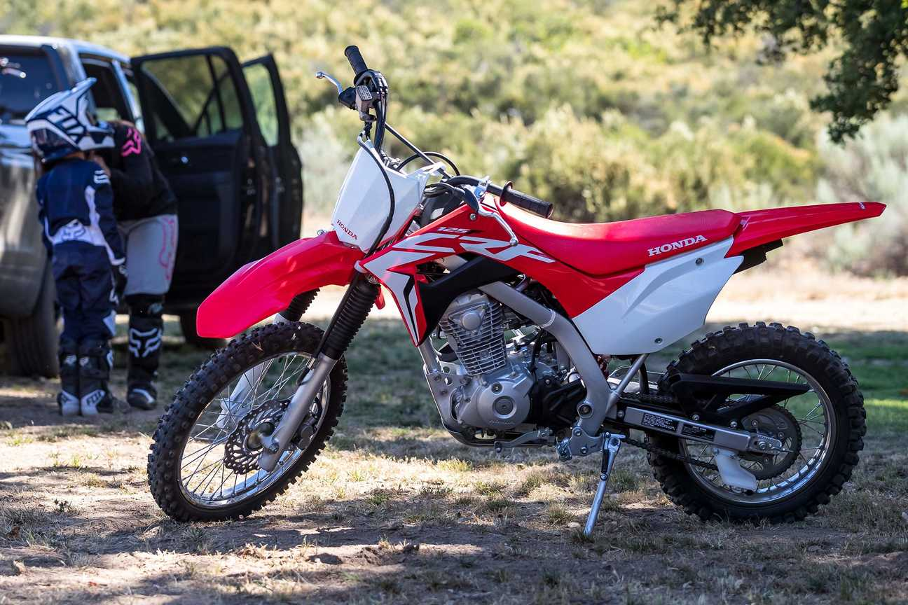 Side-on view of CRF125F, on stand in forest location. Left facing.