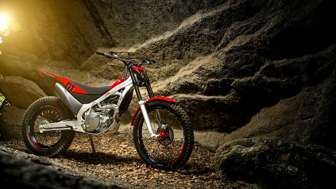 Front-threequarter view of CRF150 with rider in dirt race location.